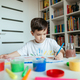 Preschooler boy draws with left hand. - PhotoDune Item for Sale