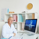 Senior Doctor Sitting at Desk in Modern Clinic - PhotoDune Item for Sale