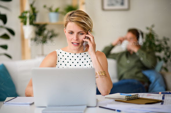 Cheerful young businesswoman with telephone indoors in home office, working - Stock Photo - Images