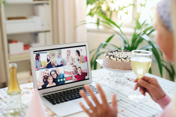 Senior woman with laptop indoors at home, celebrating distance birthday - Stock Photo - Images