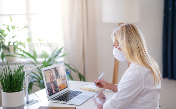 Senior businesswoman with face mask indoors in home office, having video call - Stock Photo - Images