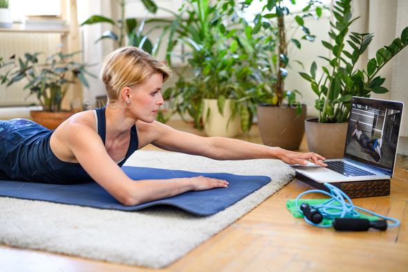 Side view of young woman doing exercise indoors at home, following vlogger - Stock Photo - Images