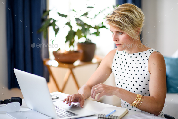 Serious young businesswoman with laptop indoors in home office, working - Stock Photo - Images