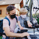 Father with small son putting bicycles on car roof for trip, wearing face masks - PhotoDune Item for Sale