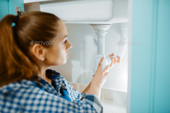 Female plumber in uniform installing drain pipe - Stock Photo - Images