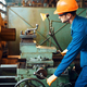 Worker in uniform and helmet works on lathe - PhotoDune Item for Sale