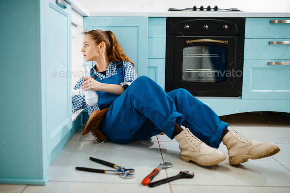 Cute female plumber in uniform holds drain pipe - Stock Photo - Images
