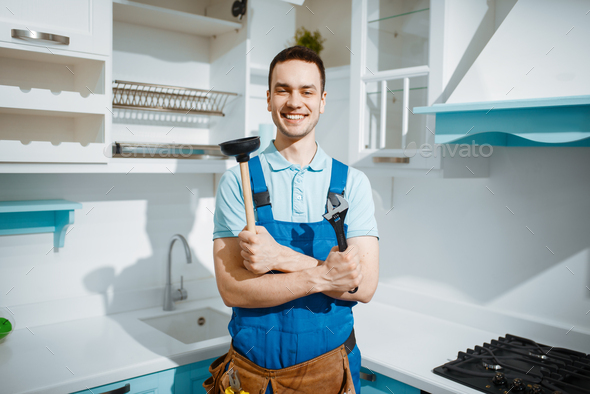 Cheerful male plumber holds wrench and plunger - Stock Photo - Images