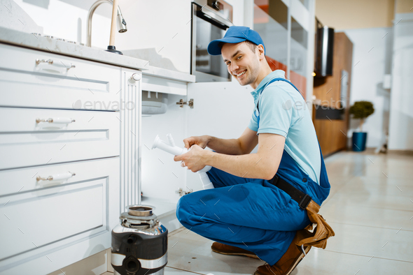 Smiling male plumber in uniform holds drain pipe - Stock Photo - Images