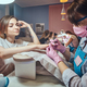 Attractive young woman with tattoo is getting nail care from manicurist. - PhotoDune Item for Sale