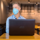 Mature businessman with mask thinking while using laptop at the coffee shop - PhotoDune Item for Sale
