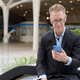Mature businessman using phone and sitting in the city outdoors - PhotoDune Item for Sale