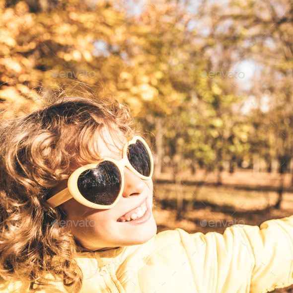 Happy child having fun outdoor in autumn park - Stock Photo - Images