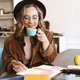 Image of smiling nice woman using cellphone while drinking coffee - PhotoDune Item for Sale
