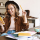 Image of woman using cellphone while studying with exercise books - PhotoDune Item for Sale