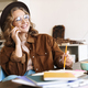 Image of woman talking on cellphone while studying with exercise books - PhotoDune Item for Sale