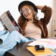 Image of smiling young woman in hat reading magazine with legs on table - PhotoDune Item for Sale