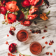 Rose wine in glasses and red spring flowers and petals - PhotoDune Item for Sale