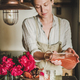 Young woman pouring rose lemonade to glasses in kitchen - PhotoDune Item for Sale