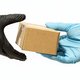 Courier man hand in protective glove delivering a package to a customer or online buyer - PhotoDune Item for Sale