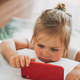 Cute toddler girl with fair hair watching mobile on bed - PhotoDune Item for Sale
