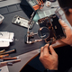 Technician carefully inspect the internal parts of the smartphone in a modern repair shop - PhotoDune Item for Sale