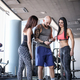 Two beautiful girls with their coach browsing something in the smartphone in modern fitness club - PhotoDune Item for Sale