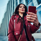 Attractive smiling woman in red jacket is posing near glass building - PhotoDune Item for Sale