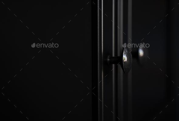 closeup of metallic door knob on black clothes cabinet - Stock Photo - Images