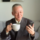 Happy mature Japanese businessman using phone while drinking coffee at home - PhotoDune Item for Sale