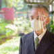 Mature Japanese businessman with mask and face shield thinking at the park - PhotoDune Item for Sale