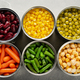 Flat lay view at canned carrots, chickpeas, kidney beans, green beans, peas and corn - PhotoDune Item for Sale