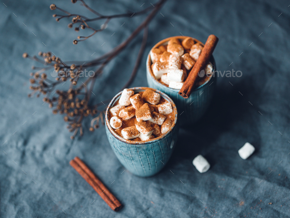 Hot chocolate with marshmallow and cinnamon in blue ceramic cups on a table - Stock Photo - Images