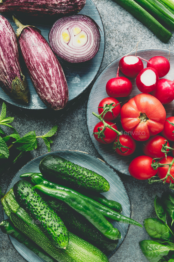 Green, red and purple various fresh vegetables on a table. Healthy eating concept. - Stock Photo - Images