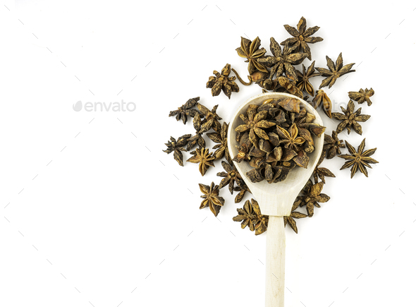 Stars of anise spread over wooden spoon isolated over white background - Stock Photo - Images