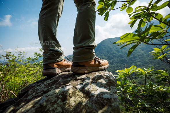 Hiker legs stand on mountain top cliff edge - Stock Photo - Images