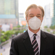 Face of mature businessman with mask for protection from corona virus outbreak against view of the - PhotoDune Item for Sale