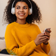Image of joyful african american woman using headphones and cellphone - PhotoDune Item for Sale
