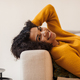 Image of joyful african american woman smiling while lying on couch - PhotoDune Item for Sale