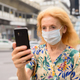 Face of blonde senior woman with mask using phone in the city outdoors - PhotoDune Item for Sale