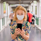 Blonde senior woman with mask using phone at the footbridge - PhotoDune Item for Sale