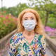 Face of blonde senior woman wearing mask for protection from corona virus outbreak at the park - PhotoDune Item for Sale