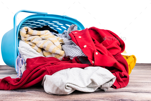 Laundry basket full of worn apparels for washing on wooden table - Stock Photo - Images