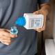 Person pouring concentrated liquid laundry detergent into measurement cap - PhotoDune Item for Sale