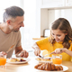 Photo of father and daughter laughing while having breakfast in kitchen - PhotoDune Item for Sale
