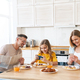 Photo of family using smartphones while having breakfast - PhotoDune Item for Sale
