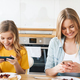 Photo of mother and daughter using cellphones while having breakfast - PhotoDune Item for Sale