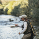 Fly fisherman using flyfishing rod in beautiful river - PhotoDune Item for Sale