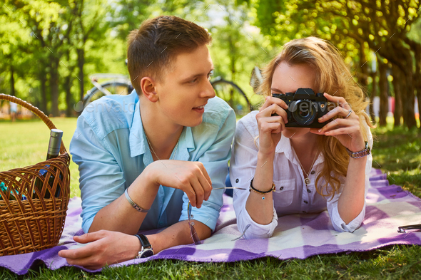 Couple using a compact photo camera at a picnic. - Stock Photo - Images