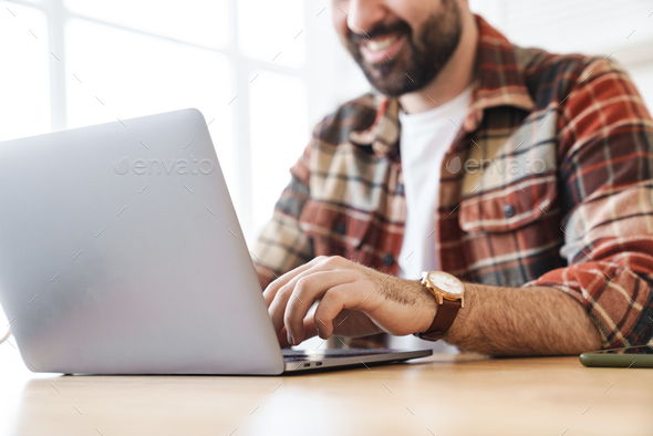 Cropped portrait of cheerful man working with laptop and smiling - Stock Photo - Images